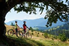 Fietsers, man en vrouw in helmen en volledig materiaal, die zich met fietsen op grasrijke heuvel bevinden royalty-vrije stock foto