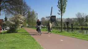 Fietsers met windmolen in Nederland stock footage
