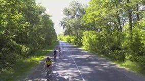 Fietsers op een de zomertraining op een bosweg stock videobeelden