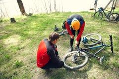 Fietsers op een halt probleem met bergfiets en reparatie stock foto's