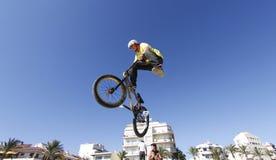 Fietsruiter die terwijl het springen tijdens de fietsenconcurrentie bedriegen royalty-vrije stock foto's