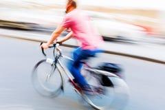 Fietsruiter op een straat in motieonduidelijk beeld Stock Foto's