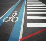 Fietssteeg in blauw met fietsersymbool samen met zebrapad Stock Afbeeldingen