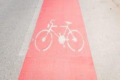 Fietssteeg in rood als voorzichtigheid op de asfaltweg wordt geschilderd met fietsteken of symbool dat royalty-vrije stock afbeelding