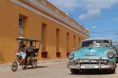 Fietstaxi en oude Amerikaanse auto in Trinidad Stock Afbeelding