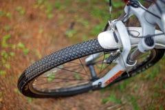 Fietswiel met loopvlakken op een vage achtergrond van gras stock foto