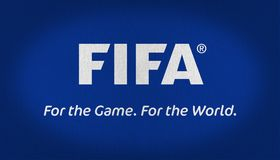 FIFA flag fabric texture. FIFA flag with a slogan in the lower part, For the Game- For the world. Flag whit text over a dark navy blue background in a fabric stock photography