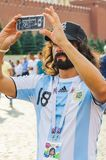 The 2018 FIFA World Cup. Argentine fan in striped white-blue t-shirts in colors of the flag of Argentina takes pictures on a smart Stock Images