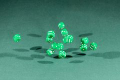Fifteen green dices falling on a green table. Fifteen green dices falling on a isolated green table stock photo