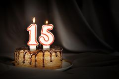 Fifteen years anniversary. Birthday chocolate cake with white burning candles in the form of number Fifteen. Dark background with black cloth royalty free stock photo