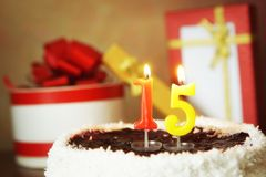 Fifteen years birthday. Cake with burning candles and gifts Royalty Free Stock Photo