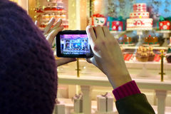 Fifth Avenue Christmas window. Woman taking pictures of a Fifth Avenue shop window festively decorated for the Christmas season. The store front windows of large royalty free stock photography