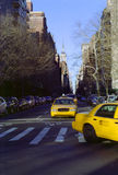 Fifth Avenue New York City Cabs USA. Fifth Avenue taxis turn onto Washington Square North on a late winter afternoon. Empire State Building distant. Greenwich stock image