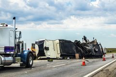 Fifth wheel RV overturned on highway with wench truck trying to get it off the road and two semis parked nearby and traffic cones royalty free stock photography