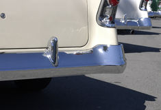 Fifties finned cars in sun. A row of American vintage cars from the 1950s with gleaming chrome, photgraphed from behind Royalty Free Stock Photos