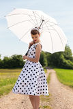 Fifties look with petticoat dress, hairband and sunshade in the Royalty Free Stock Photography