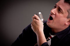 Fifties style singer on a dark background Royalty Free Stock Images