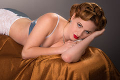 Fifties styled beautiful redheaded woman in satin lingerie Royalty Free Stock Images