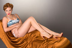 Fifties styled beautiful redheaded woman in satin lingerie Stock Photo