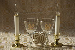 Fiftieth (50th) Anniversary. Antique Fiftieth Golden anniversary glasses and candles with white and gold background Stock Photos
