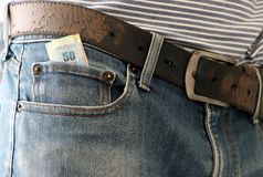 Fifty baht banknote of Thailand in the mini pocket of jeans with belt. Fifty baht banknote of Thailand in the mini pocket of blue jeans with belt Stock Photos