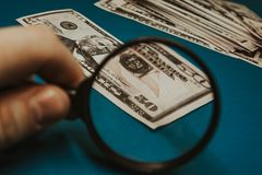 Fifty dollar bill on a blue background being studied through a magnifying glass. Fifty dollar bill on a blue background being studied through a magnifying glass royalty free stock photos