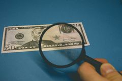 Fifty dollar bill on a blue background being studied through a magnifying glass. stock image