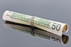 Fifty dollar bill is rolled into elegant women`s silver ring Royalty Free Stock Photo