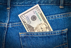 Fifty dollars bill sticking out of the jeans pocket Royalty Free Stock Photography