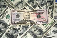 Fifty dollars among hundred dollar bills. A fifty dollar bill with hundred dollar bills in the background Stock Photo