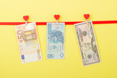 Fifty dollars, zloty and euro hangs on the clothespins, yellow background Stock Image
