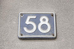 Fifty eight number in the wall of a house Royalty Free Stock Photography