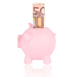 Fifty euro banknote and coinbank. Pink piggy bank with 50 euro banknote on a white background Stock Images