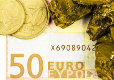 Fifty euro banknote with euro coins and golden nuggets stock image