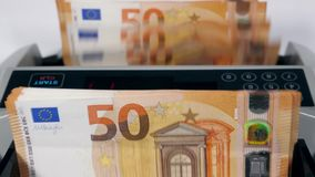 Fifty-euro banknotes are getting put into the machine and counted. 4K stock video footage