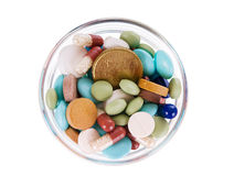 Fifty euro cents in saucer full of pills. Fifty euro cents in glass saucer full of different pills on white background royalty free stock images