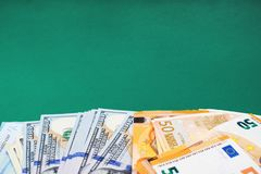 Fifty euro and hundred dollar bills on green background. royalty free stock photo