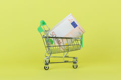 Fifty euro in the shopping pushcart, yellow background. Fifty euro in the shopping pushcart, on the yellow background Royalty Free Stock Photo