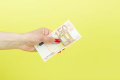 Fifty euro in the woman`s hand, yellow background Stock Photography