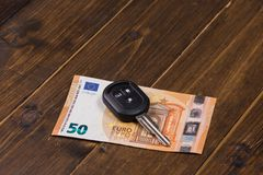 Fifty euros banknote and car keys. On wooden background stock photo