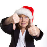 Fifty Fifty. Older senior business woman's arthritic hand with knobbly fingers in a 50 - 50  hand gesture. Wearing a santa hat Royalty Free Stock Photos