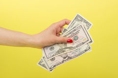 Fifty, five and one dollars in the woman`s hand, yellow background Royalty Free Stock Image