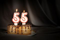 Fifty five years anniversary. Birthday chocolate cake with white burning candles in the form of number Fifty five. Dark background with black cloth royalty free stock photography