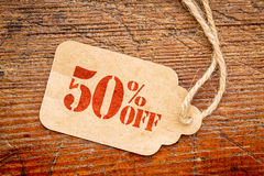 Fifty percent off reduced price -  paper tag. Fifty percent off discount  - a paper price tag against rustic wood - sale concept Stock Photography