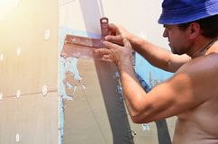 Fifty years old manual worker with wall plastering tools renovating house. Plasterer renovating walls and corners with spatula and plaster. Wall mash royalty free stock image