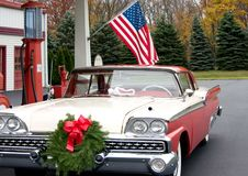 Fiftys Christmas. This is a mid 1950s car at a gasoline service station with a wreath on the front of the grill Royalty Free Stock Photos