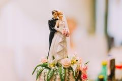Figürchen der Braut und des Bräutigams auf Hochzeitskuchen Stockfotografie