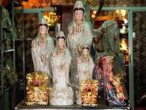Fig?rchen der G?ttin der Gnade, des Guan Yins und des Gottes des Verm?gens, Cai Shen, an einem Taoistgebets-Einzelteilspeicher stockbilder