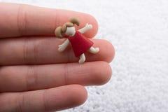 Figürchen des kleinen Mädchens in der Hand auf weißem Hintergrund Lizenzfreie Stockfotos