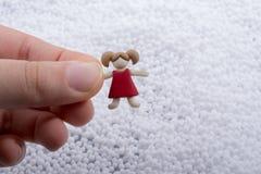 Figürchen des kleinen Mädchens in der Hand auf weißem Hintergrund Lizenzfreie Stockfotografie